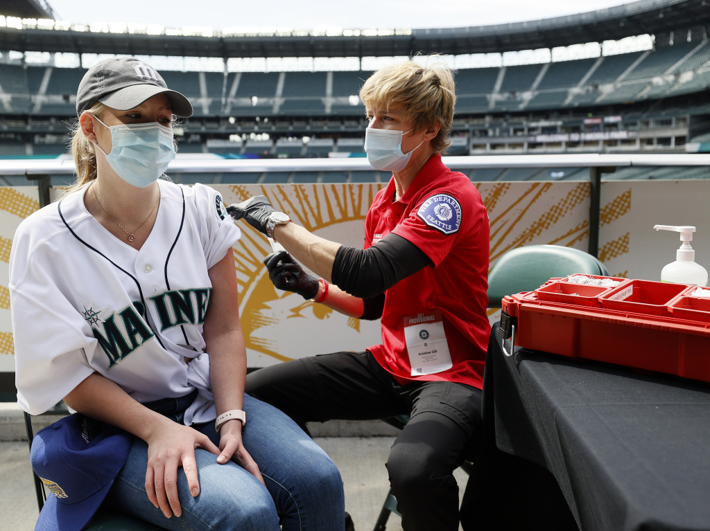Sydney Porter of Bellevue, Wash., receives her COVID-19 vaccination from Kristine Gill, with the Seattle Fire Department's Mobile Vaccination Teams, before the game between the Seattle Mariners and the Baltimore Orioles at T-Mobile Park on May 5 in Seattle. A late spring COVID-19 surge has filled hospitals in the metro areas around Seattle.
