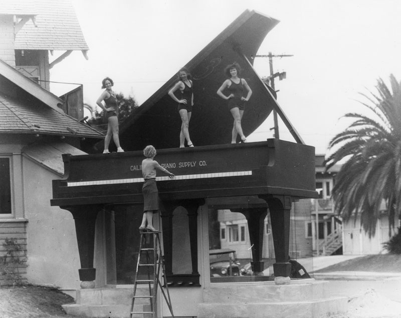 A giant grand piano marks the entrance of the California Piano Supply Co., which was renamed the Big Red Piano in the 1960s. (circa 1920s - '30s) (Photograph via Los Angeles Public Library Collection)