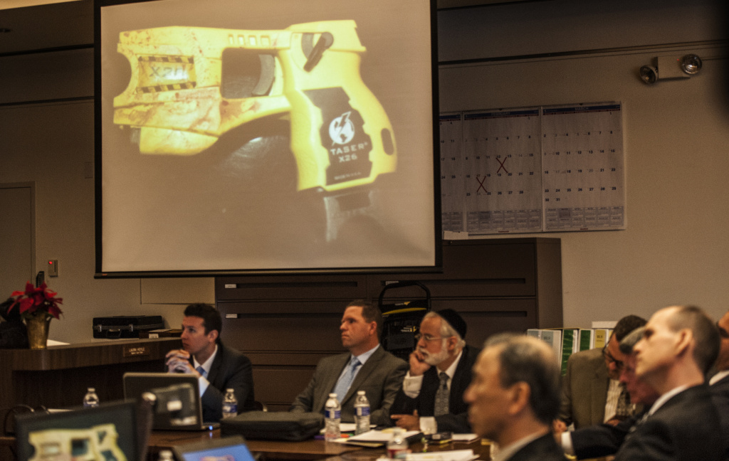 Orange County District Attorney Tony Rackauckas shows the jury an image of taser gun like the one that Fullerton police officer Jay Cicinelli used to strike Kelly Thomas during an encounter at the Fullerton Transportation Center on July 5, 2011 as Cicinelli sits below the image under the handle of the gun on Monday, Dec. 2, 2013 in Santa Ana, Calif.  Rackauckas  told jurors that former Fullerton officers Cicinelli and Manuel Ramos were responsible for the death of 37-year-old Kelly Thomas in July 2011. Thomas, whose family says was schizophrenic, died five days after the violent confrontation with six officers who responded to a call about a man jiggling car door handles in a transit center parking lot. Ramos is charged with second-degree murder and involuntary manslaughter. Cicinelli is charged with to involuntary manslaughter and use of excessive force.  Barnett portrayed Thomas as an unpredictably violent person in his opening statements.