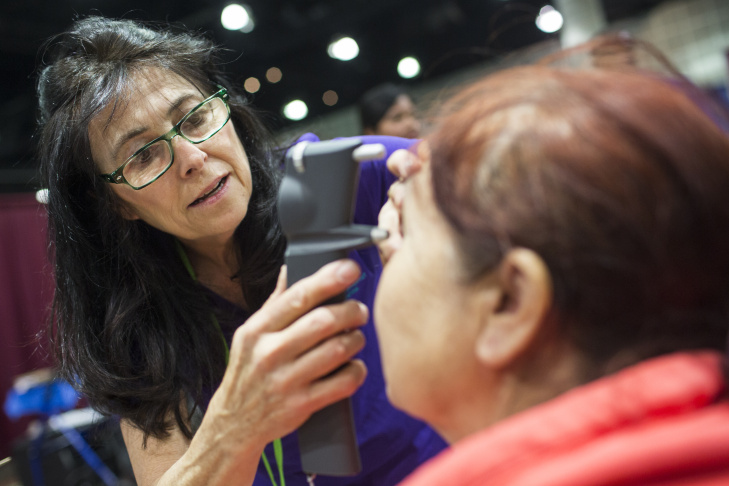 Thelma Goodlitt tries on eyeglasses during the three-day Pathway to Health free clinic at the Los Angeles Convention Center.
