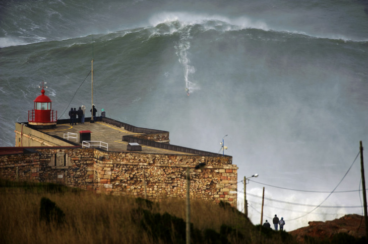 This photo released Tuesday Jan. 29, 2013, by Nazare Qualifica organization, US surfer Garrett McNamara rides a wave off Praia do Norte beach in Nazare, Portugal, on Monday Jan. 28, 2013.  McNamara is said to have broken his own world record for the largest wave surfed when he caught this wave reported to be around 100ft, off the coast of Nazare on Monday.  If the claims are verified, it will mean that McNamara, who was born in Pittsfield, Massachusetts but whose family moved to Hawaii's North Shore when he was aged 11, has beaten his previous record, which was also set at Nazare, of 23.77 meters (78 feet) in November 2011.