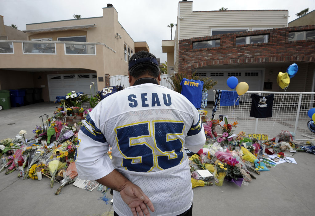 San Diego Chargers fan Jerry Lopez looks over a memorial set-up in the driveway of the house of former NFL star Junior Seau Thursday, May 3, 2012, in Oceanside, Calif.