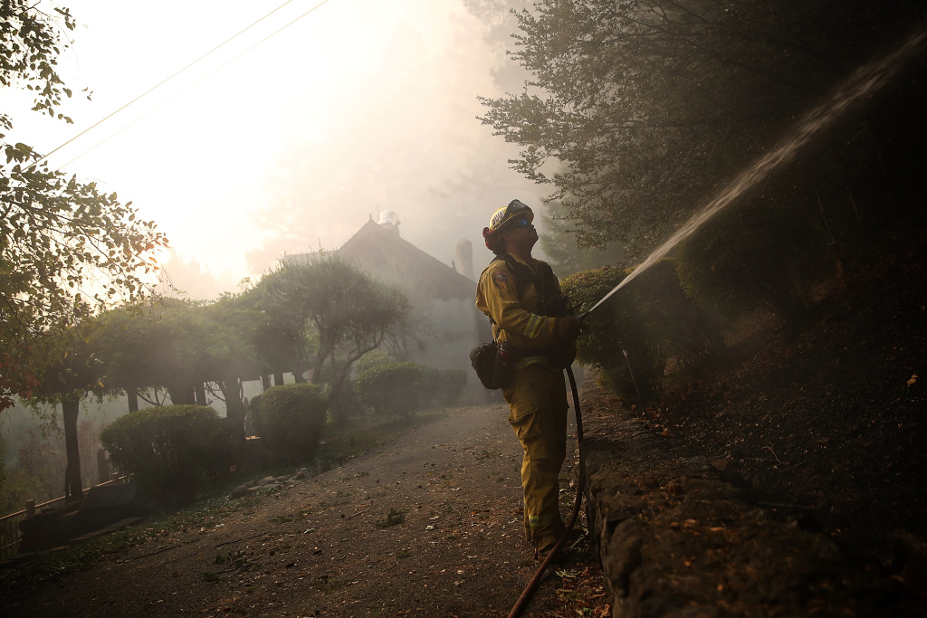 A CalFire firefighter uses a hose to battle the Tubbs Fire on October 12, 2017 near Calistoga, California.
