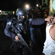 An elite police officer arrests an alleged member of the Mara Salvatrucha gang in San Juan Opico, La Libertad, 40 km West of San Salvador, El Salvador on April 10, 2008. U.S. deportation policies in recent decades have resulted in large numbers of former U.S. gang members landing in El Salvador and other Central American countries; now, many families and children are fleeing gang violence there.