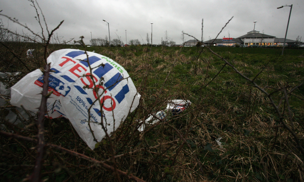 File: A plastic bag is caught in bushes outside a supermarket.