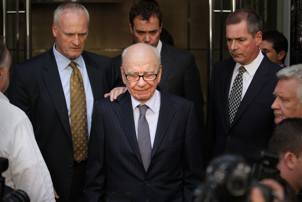 News Corp. Chairman Rupert Murdoch (C) looks down as he leaves the One Aldwych Hotel surrounded by his personal security team to speak with reporters after meeting with the family of murdered school girl Milly Dowler on in London, England.