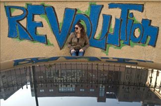 An Egyptian woman stands in front of graffiti reading 'Revolution' at Cairo's Tahrir Square, the epicentre of the popular revolt that drove veteran strongman Hosni Mubarak from power after 30 years, on Feb. 17, 2011.