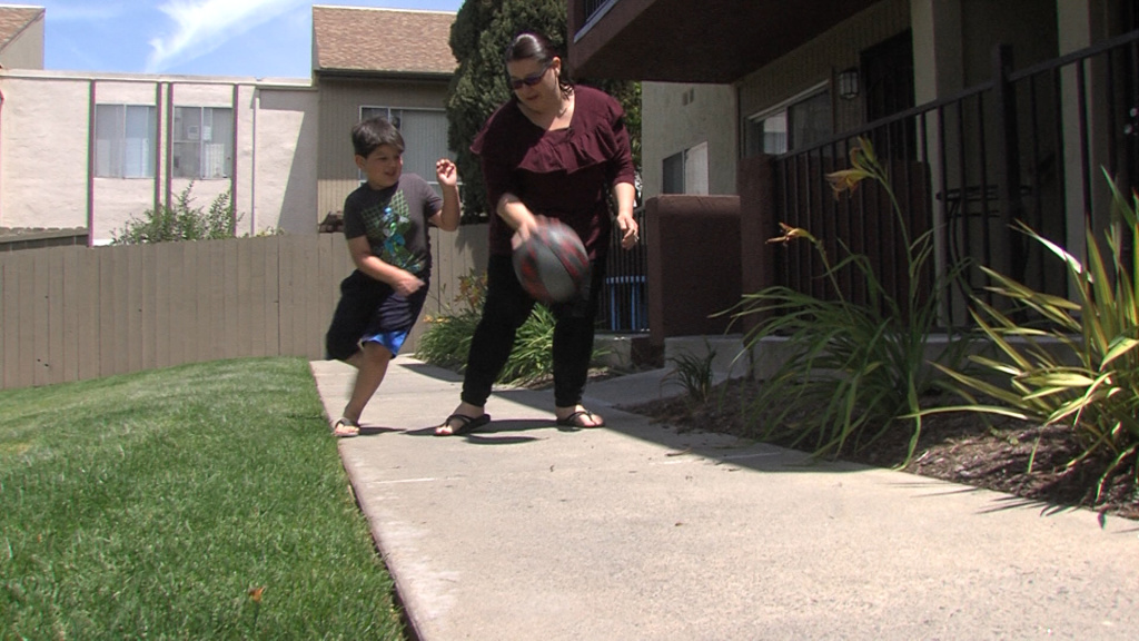 Charlene Holkenbrink-Monk plays ball with her son Owen outside their San Diego apartment, May 8, 2018.