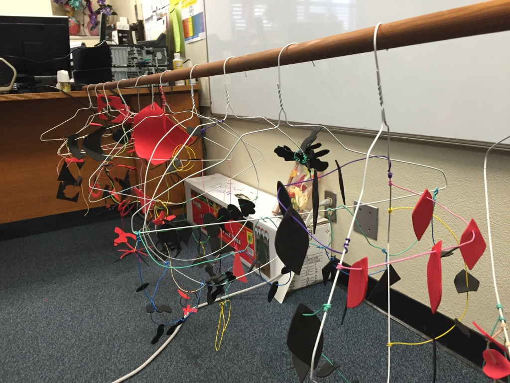 During visual arts training, teachers cut different shapes out of foam sheets to make mobiles.