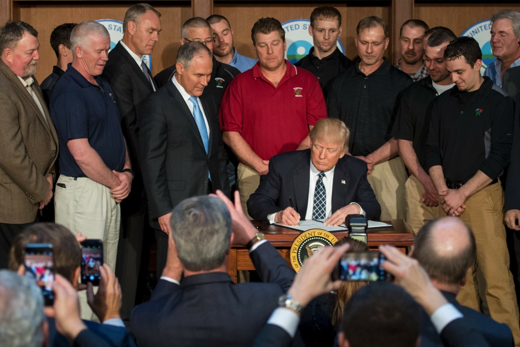 Surrounded by miners from Rosebud Mining, President Donald Trump signs the Energy Independence Executive Order at the Environmental Protection Agency headquarters in Washington, DC, on March 28, 2017. Trump claimed an end to the