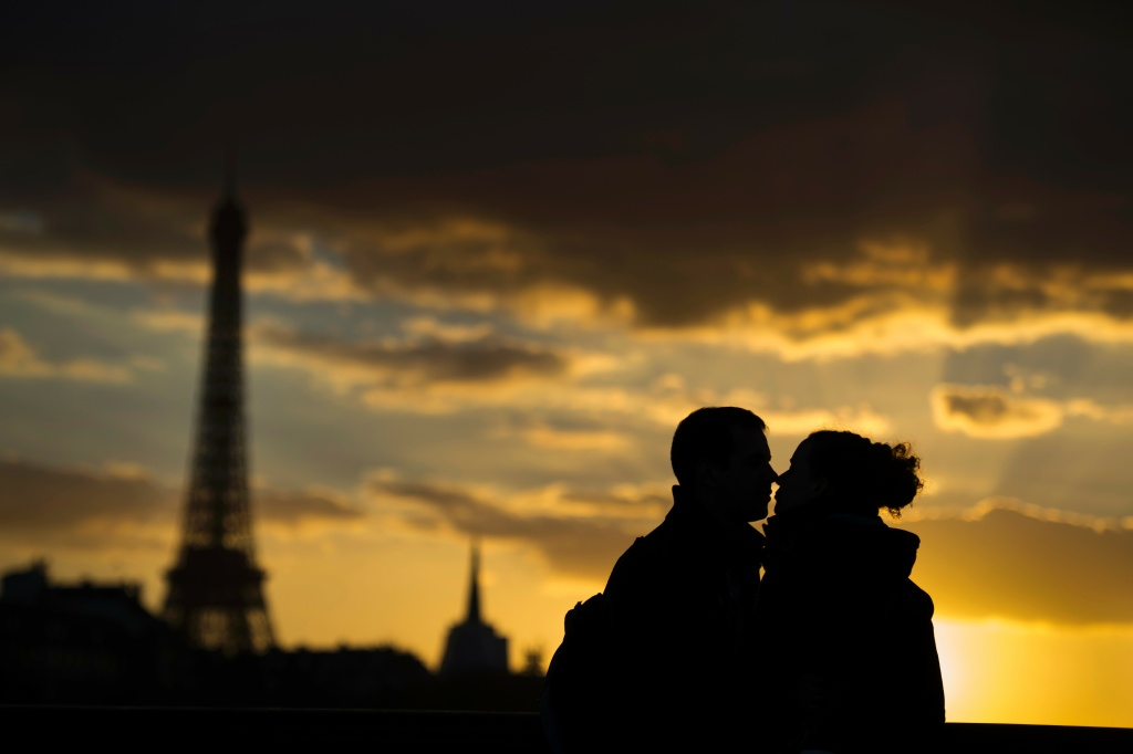 Two people kiss in front of the Eiffel Tower at sunset on March 5, 2014 in Paris.