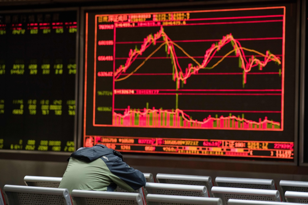 A man rests as he keeps an eye on stock price movements displayed on a screen at a securities company in Beijing on March 23, 2018. Asian markets plunged on March 23 following a sell-off in New York as Donald Trump sparked fresh trade war fears by imposing huge tariffs on Chinese imports and Beijing unveiled its own measures against US goods.