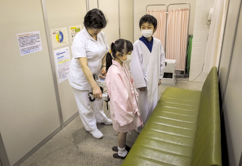 Reina Endo, 7, and her brother Shun Endo, 10, are prepared to be screened for radiation, on March 09, 2012 in Minamisoma in Fukushima Prefecture, Japan. Those rallying against nuclear power in Japan are worried about radiation exposure and possible effects on community health. The 12-mile radius around the Fukushima plant remains unlivable more than a year later.