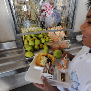 A cafeteria worker supervises lunches fo