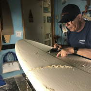 Rich Harbour shapes a blank surfboard deck in the workshop in the back of his shop Harbour Surfboards