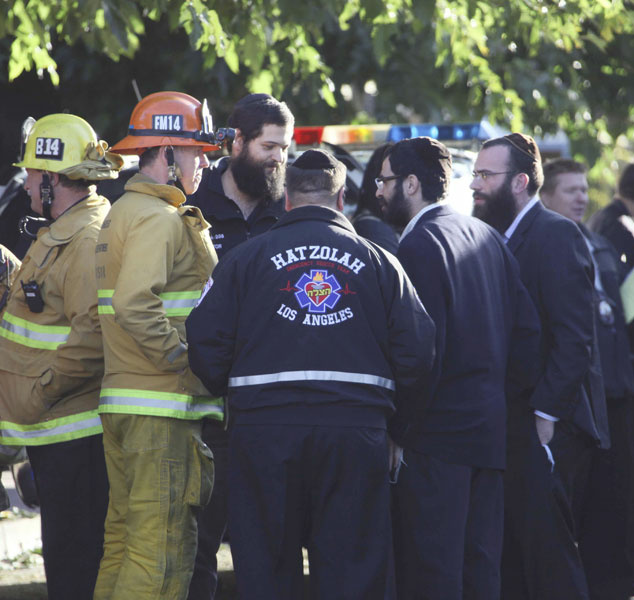 Los Angeles firefighters and synagogue parishioners huddle at the scene in Los Angeles where a gunman shot and wounded two men in the parking garage of a North Hollywood synagogue early Thursday, Oct. 29, 2009. Jewish schools and temples were put on alert in case it was not a lone attack, authorities said.