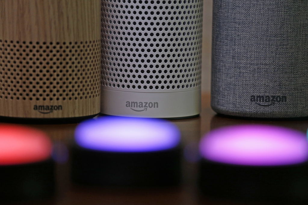 FILE - In this Sept. 27, 2017, file photo, Amazon Echo and Echo Plus devices, behind, sit near illuminated Echo Button devices during an event announcing several new Amazon products by the company in Seattle.  Amazon is expanding its home-security business by buying Ring, the maker of Wi-Fi-connected doorbells. The deal comes months after the online retailer started selling its own Wi-Fi-connected indoor security cameras, which work with its voice-assistant Alexa.