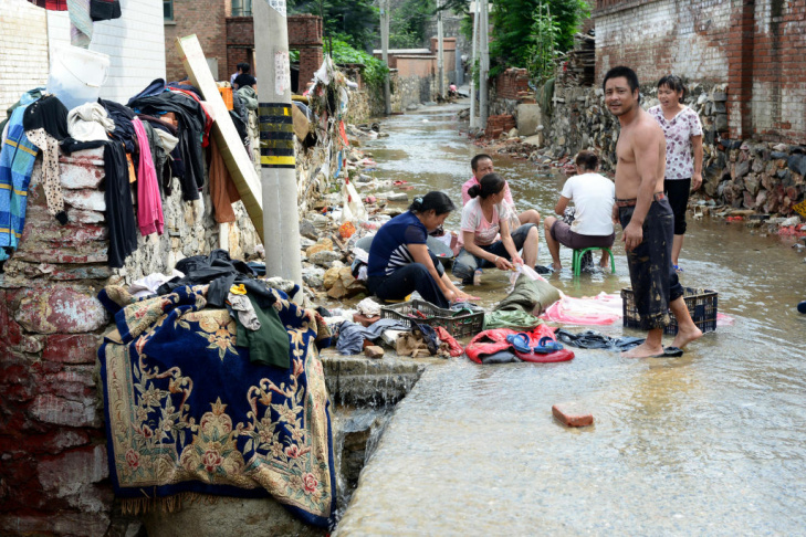 This picture taken on July 23, 2012 shows Chinese residents cleaning up after heavy rains in Beijing. Beijing residents expressed fury on July 22 after the worst rains to hit the Chinese capital in more than 60 years left at least 37 people dead,