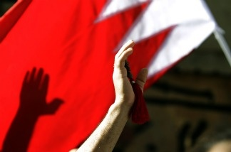 Bahraini Shiite wave a Bahrain flag as they attend the funerals of Bahiya al-Aradi in central Manama.