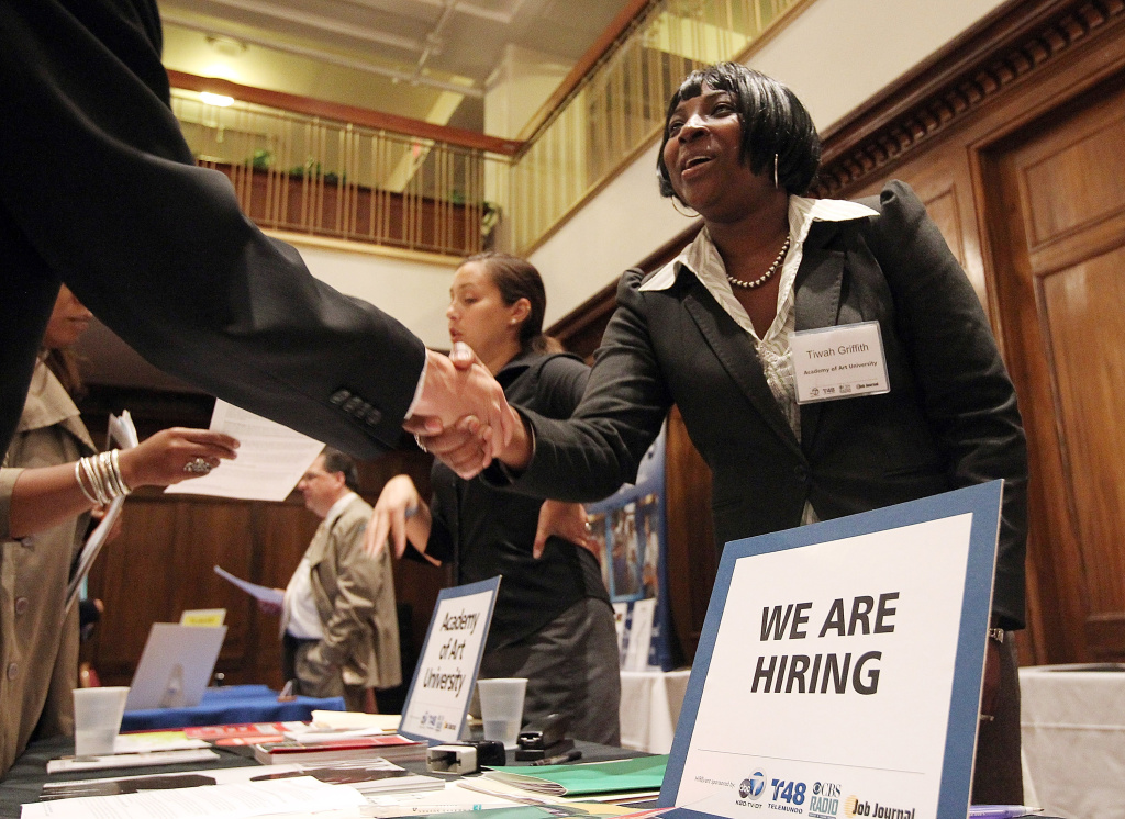 A job seeker shakes hands with a recruiter during the San Francisco Hirevent job fair at the Hotel Whitmore in San Francisco, California.