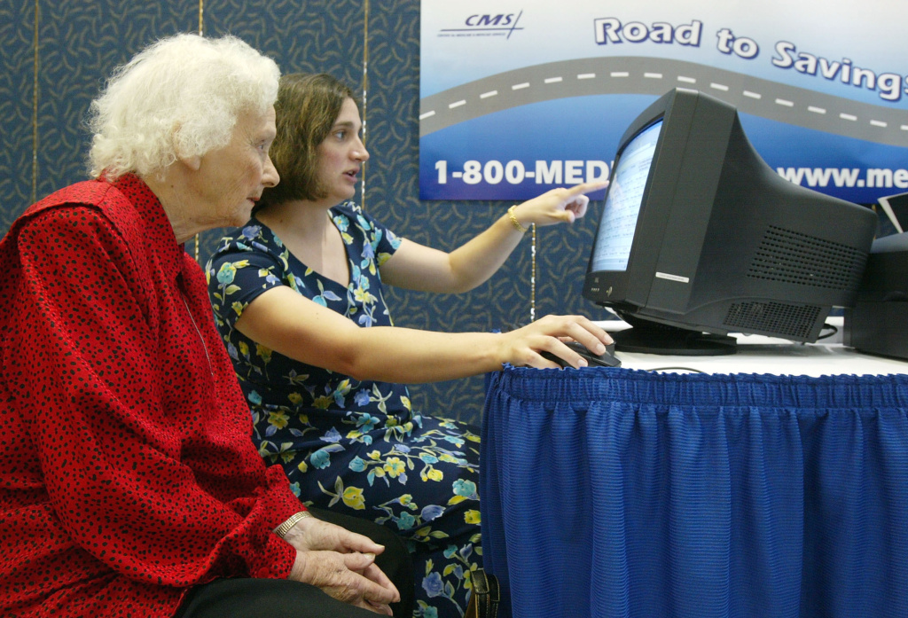 Center for Medicate & Medicaid Services' Web Site Project Management Director Ana Nunez-Poole (R) helps Medicare recipient Gladys Parrish (L) to compare Medicare-approved drug prices on the internet May 3, 2004 in Washington, DC.