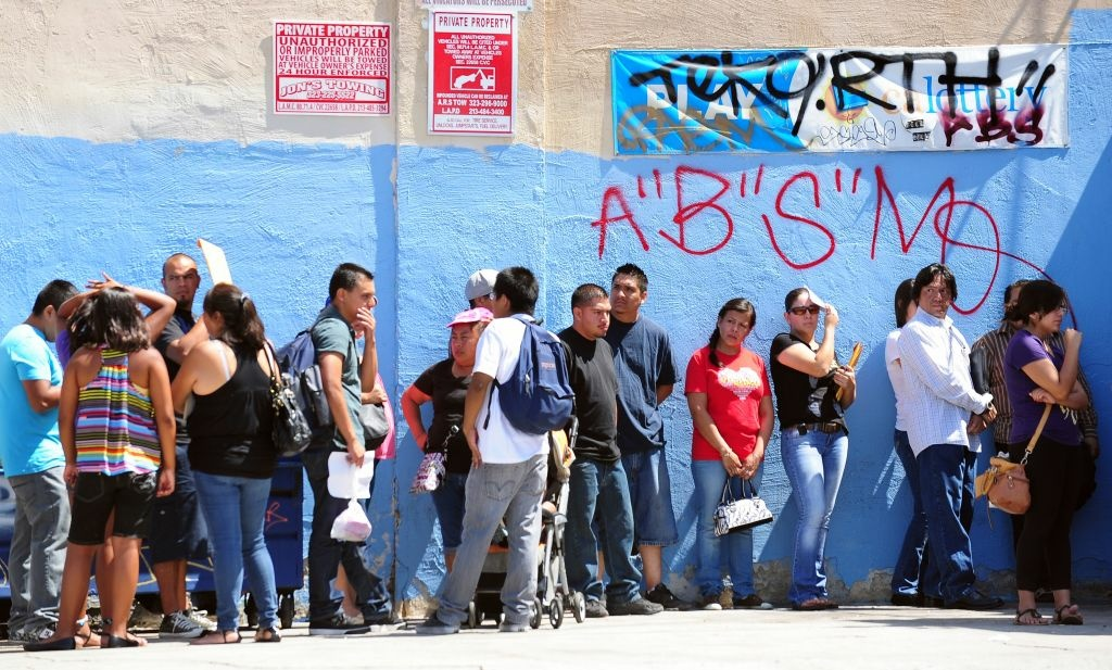 This Aug. 15, 2012 file photo shows young people waiting in line to enter the Coalition for Humane Immigrant Rights of Los Angeles (CHIRLA) office in California, on the first day of the Deferred Action for Childhood Arrivals (DACA) program. A report released Thursday by the nonpartisan Pew Research Center estimates more than 2 million immigrants in the country illegally lived in the New York and Los Angeles metropolitan areas in 2014.
