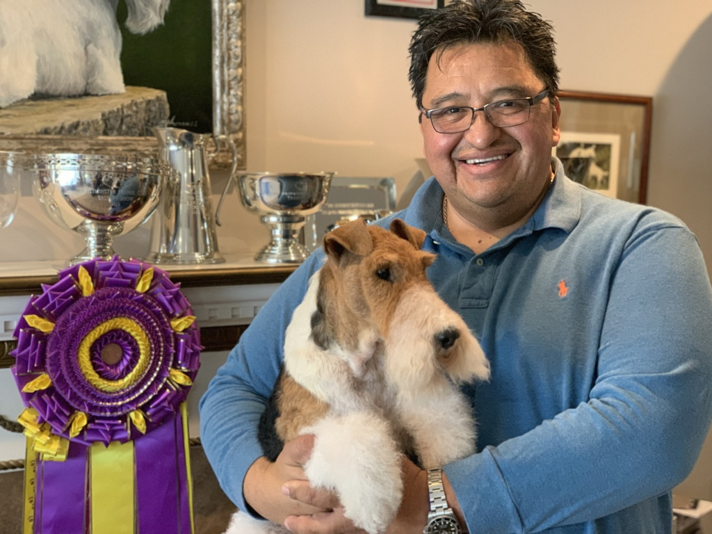 King, a wire-fox terrier, held by his handler Gabriel Rangel at his home in Rialto next to their Westminster ribbon for Best in Show.