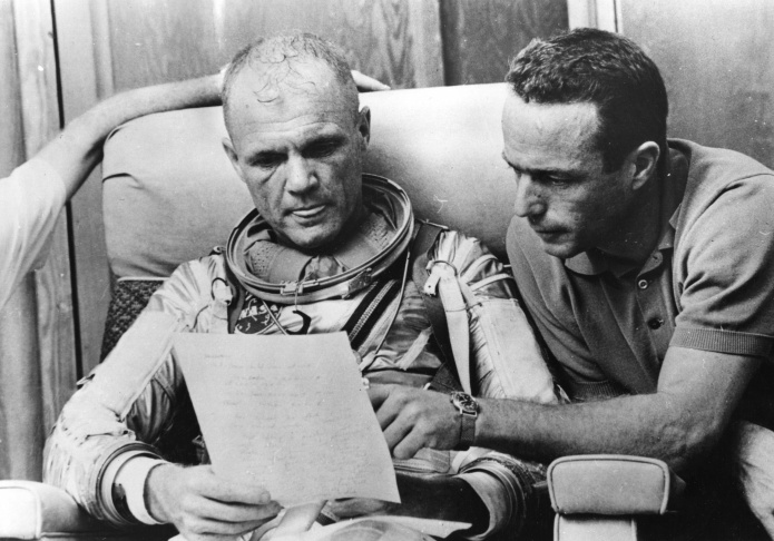 Astronaut Scott Carpenter is shown gesturing with one hand after donning his space suit in Hangar S prior to being shot into orbit at Cape Canaveral, Florida, May 24, 1962. On his right chest is a large reflecting mirror which aids in reading instruments in his Aurora 7 capsule.