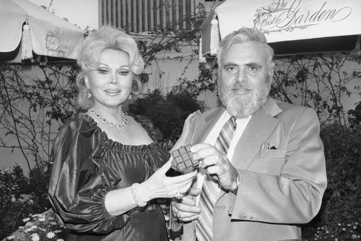 Actress Zsa Zsa Gabor, a native of Hungary, holds Rubik's Cube, a color and geometric puzzle game just being introduced in this country, during meeting with press on Monday, May 6, 1980 in Los Angeles. At right is Dr. Solomon W. Golomb of the University of Southern California, who has authored books on mathematical probabilities and is the inventor of math games and puzzles.