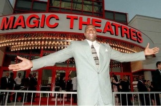 Former Los Angeles Lakers player Earvin 'Magic' Johnson stands in front of the 12-screen movie theatre that he built and financed during the theatre's grand opening.