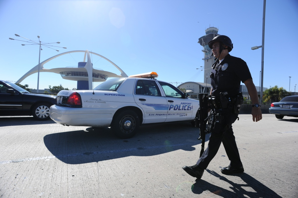 A police officer walks through Los Angeles International Airport after a shooting on November 1, 2013. A man pulled a semi-automatic rifle from a bag and opened fire at a security checkpoint,. killing a TSA officer and wounding others, according to police.