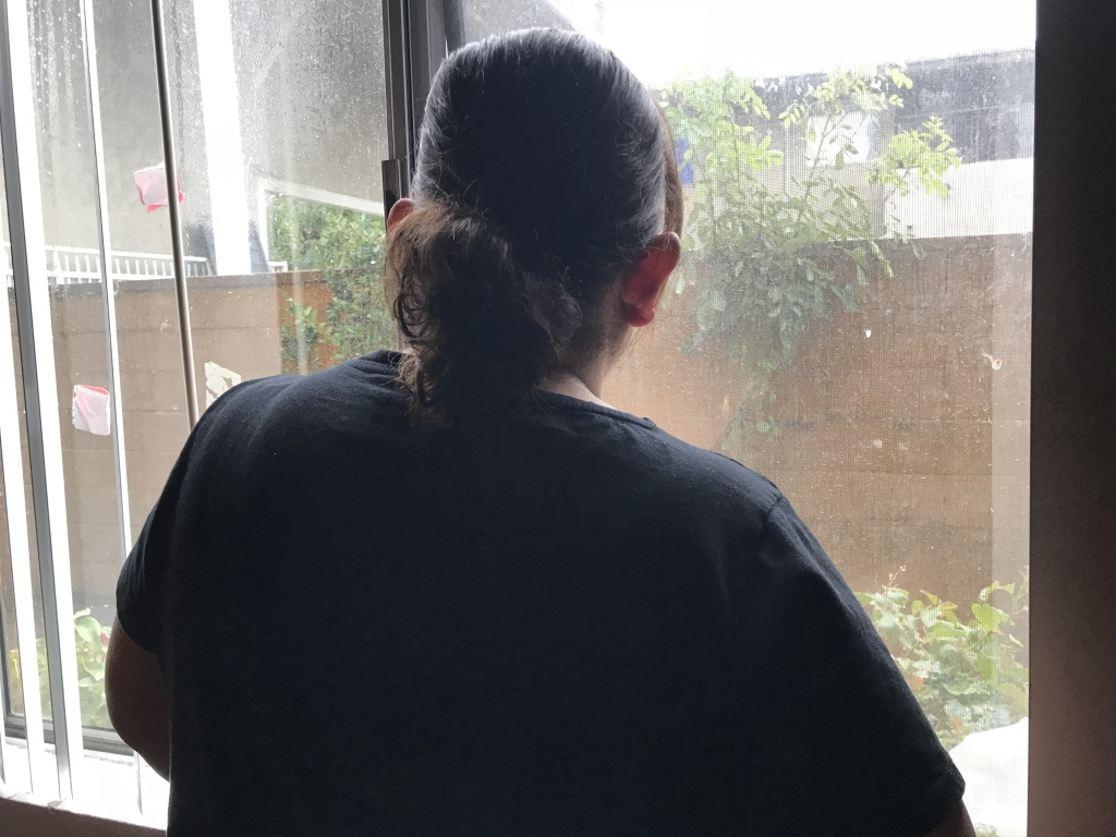 Lizeth looks out the window of her apartment in Los Angeles, Dec. 6, 2018.