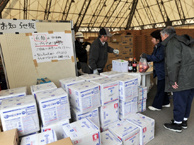 An elderly Japanese couple receives food and drinks from a distribution center in Kamaishi on Sunday.