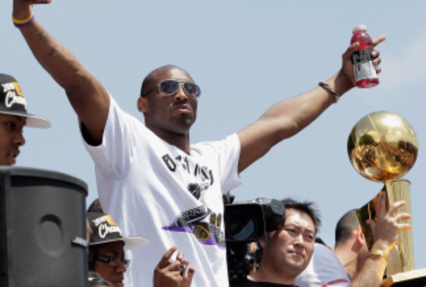 Los Angeles Lakers guard Kobe Bryant (L) waves to the crowd while riding in the victory parade for the the NBA basketball champion team on June 21, 2010 in Los Angeles, California.