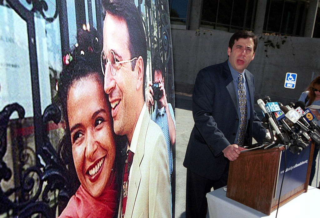 Daniel Pearl's childhood friend Daniel Gill, 38, speaks to reporters after a memorial service for the slain reporter,  next to a 1999 wedding photo of Pearl and his wife Mariane at Skirball center in Los Angeles 10 March 2002.