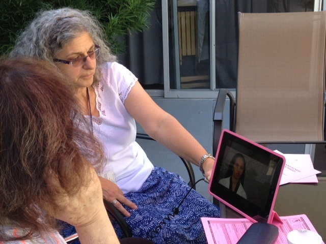 Ellen Stirling shows a nursing home patient a video on end-of-life choices.