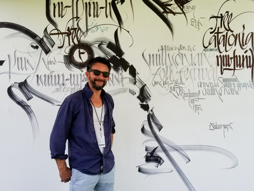 Armenian artist Ruben Malayan stands in front a poster at his booth at the Smithsonian Folklife Festival in Washington, D.C.