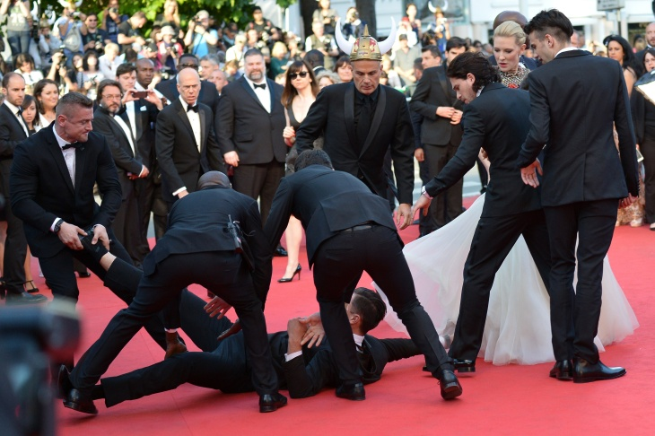 Ukrainian journalist Vitalii Sediuk is taken away by a minder after he tried to slip under U.S. actress America Ferrera's dress as she arrived for the screening of the animated film 'How to train your Dragon 2' at the 67th edition of the Cannes Film Festival in Cannes, southern France, on May 16, 2014. On Wednesday, Sediuk was arrested after accosting Brad Pitt on another red carpet, this time in Hollywood for the premiere of