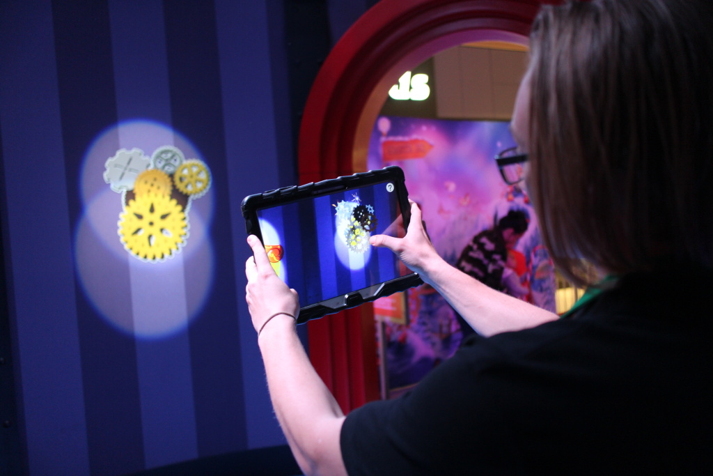 HGTV Santa HQ castmember, Jakob Hatch, demonstrates an augmented reality feature of the attraction at Lakewood Center mall.