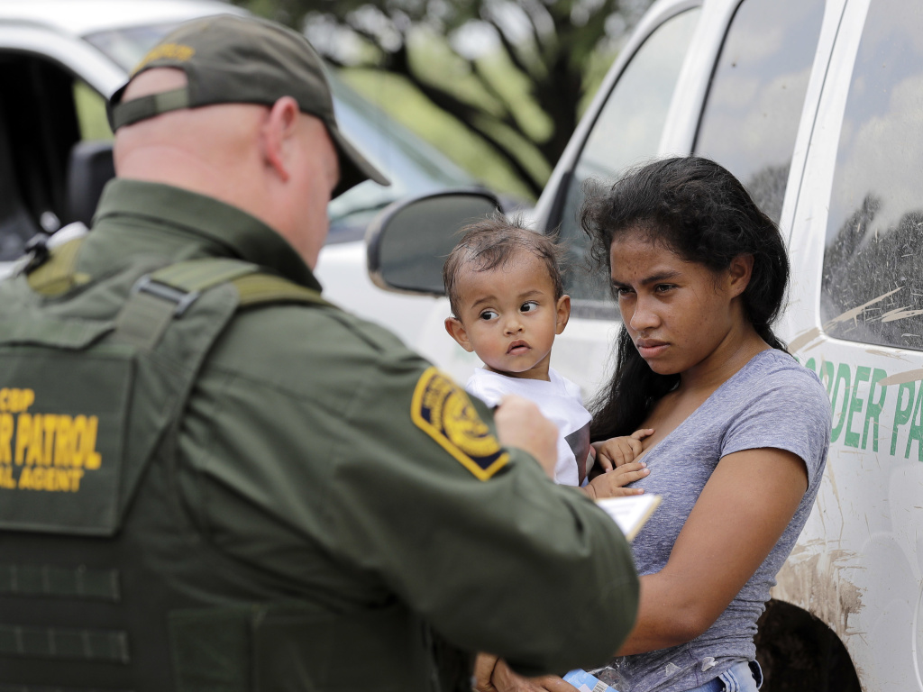 A migrant family with a border patrol officer