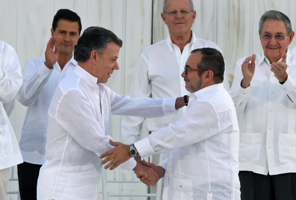 Colombian President Juan Manuel Santos (2-L) and the head of the FARC guerrilla Timoleon Jimenez, aka Timochenko, shake hands during the signing of the historic peace agreement between the Colombian government and the Revolutionary Armed Forces of Colombia (FARC), in Cartagena, Colombia, on September 26, 2016