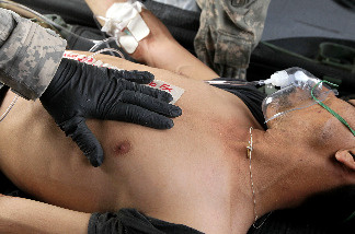 U.S. Army Staff Sgt. James Shields from Charlie Co. Sixth Battalion, 101st Airborne Combat Aviation Brigade, Task Force Shadow examines a wounded Afghan National Army soldier as he is flown to the hospital in a MEDEVAC helicopter on June 27, 2010 in Kandahar, Afghanistan.