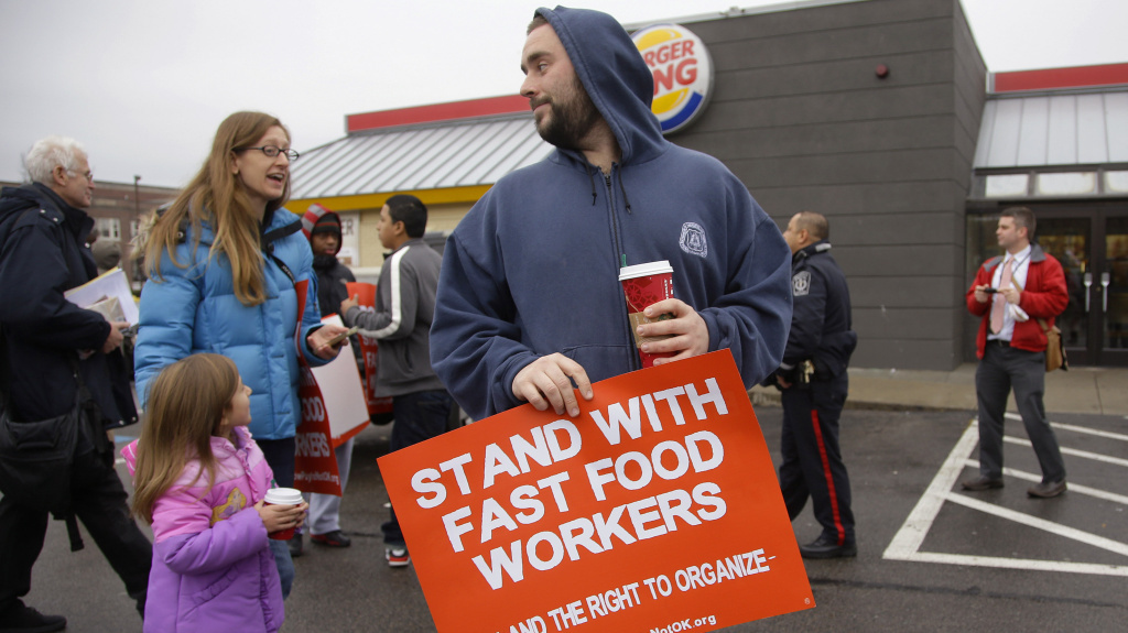 Protesters in Boston march in the parking lot of a Burger King as part of a nation-wide protest supporting higher wages for workers in the fast-food industry.