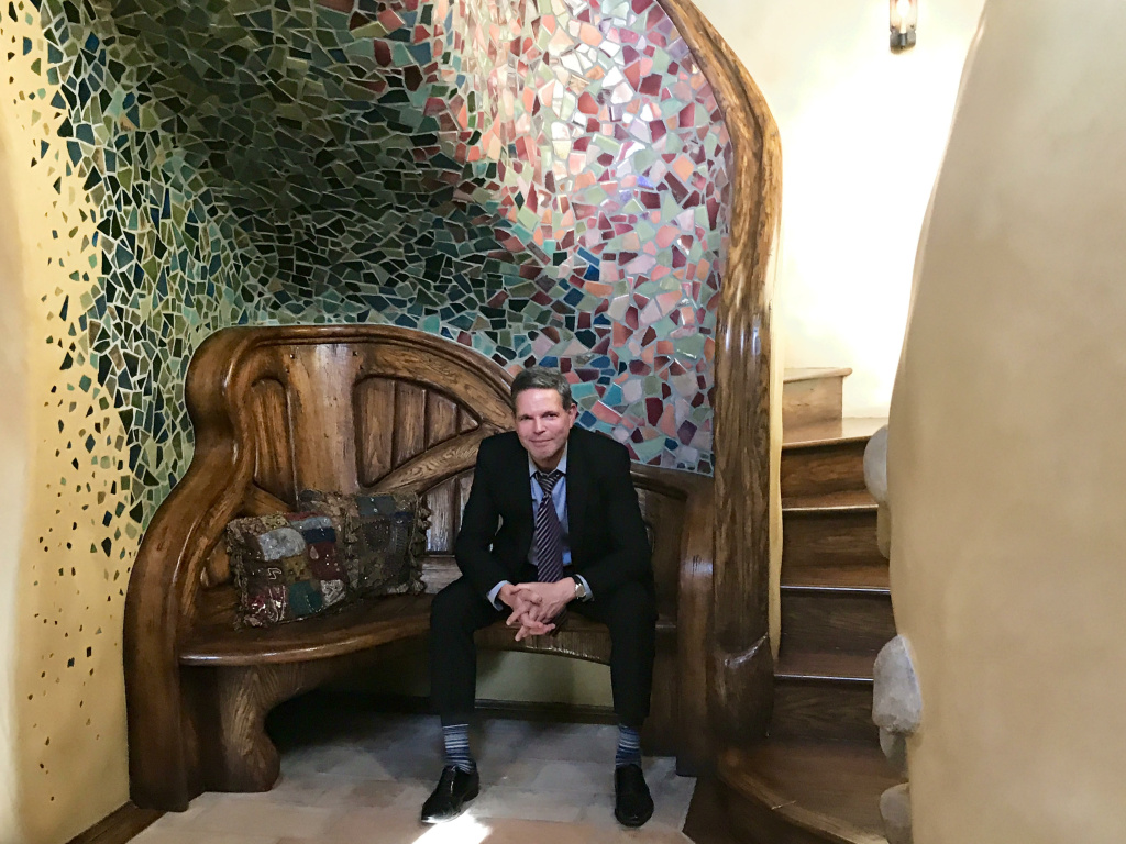 Michael Libow seated in front of the broken tile mosaic and staircase that greets guests from the front door of his Witch home.