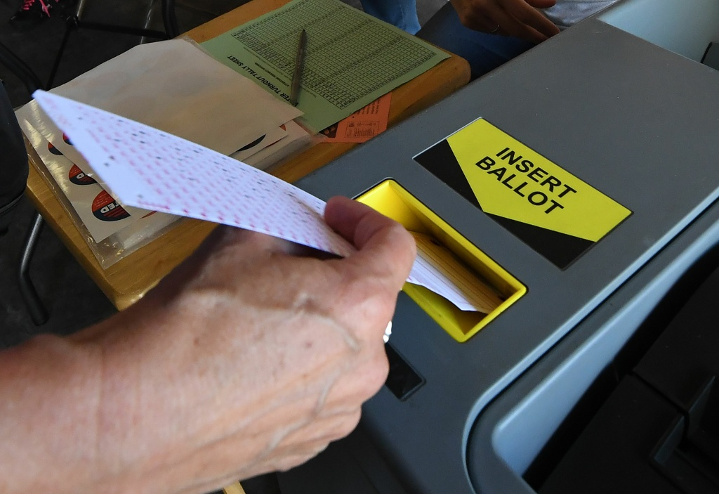 A woman inserts her ballot into the machine after voting at a Lifeguard headquarters that doubles as a polling station during the midterm elections.