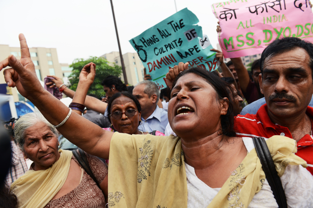 An Indian woman shouts slogans calling for the death penalty of four men convicted of rape and murder outside the Saket courthouse in New Delhi on September 13, 2013. A judge sentenced four men to death September 13 for the fatal gang rape of an Indian student on a bus last December, triggering applause inside the packed courtroom.
