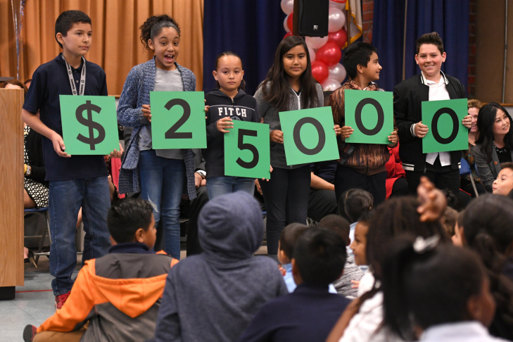 Students from Washington Elementary and the Milken Family Foundation hold signs spelling out $25,000, the amount of money awarded to their teacher Katherine Shaw on March 3, 2017. Shaw received a Milken Educator Award, one of the most prestigious honors for educators.