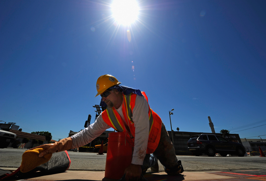 Brick layer Allan Sandahl, of Los Angeles City Construction Forces Division, wipes the bricks with a wet sponge under the sun while working on a sidewalk construction project on August 25, 2010 in Los Angeles, California.