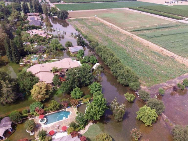 This June 25, 2017, photo taken by an unmanned aerial vehicle and released by the Tulare County Sheriff's Office shows flooding from the Kings River at the Kings River Golf and Country Club in Kingsburg, Calif. Authorities say 90 homes remain under mandatory evacuation orders following levee breaches along the Kings River in Central California. The Kings River began to flood Wednesday about 25 miles (40 kilometers) north of Fresno as temperatures soared, melting snow in the Sierra Nevada and sending it downstream.