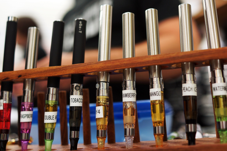 A variety of  .electronic cigarette flavors are viewed for sale at Vape New York. Electronic cigarettes, or e-cigarettes, are battery powered devices that vaporizes a nicotine laced liquid solution into an aerosol mist which simulates the act of tobacco s